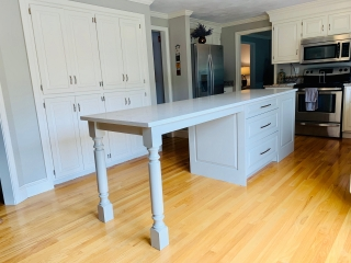 Gray kitchen island with traditional spool island legs.
