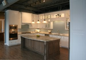 White kitchen cabinets with raised panel doors coupled with stained maple island